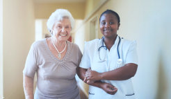 caregiver holding the hands of elder woman